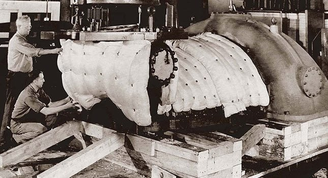 Building turbines in the big manufacturing plant of the De Laval Steam Turbine company in Trenton. The top half of a turbine casing is in the process of being insulated with fiberglass bats.