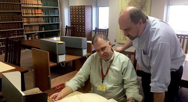 Director of the New Jersey State Archives Joseph Klett (standing) and Reference Assistant Jon Bozzard, review a historical document.