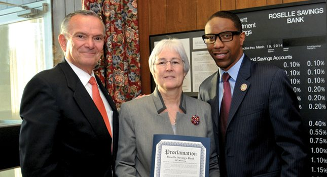 Roselle Mayor Jamel C. Holley (right) presents a 125th anniversary proclamation to bank Board Chairman William Fredericks, CPA, and President/CEO Jill Schafhauser.
